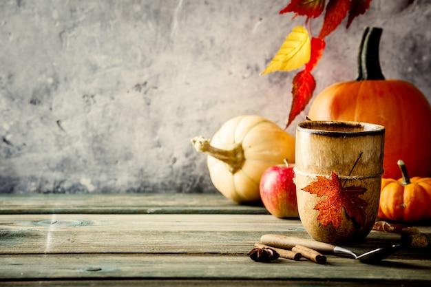 Priorità bassa di autunno su tabel di legno contro la vecchia parete dell'annata di condizione della ruggine