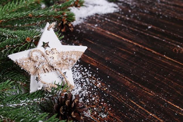 Priorità bassa di concetto di natale, decorazione fatta a mano della stella ed alberi di natale verdi su una tabella di legno, tratteggiata da neve bianca