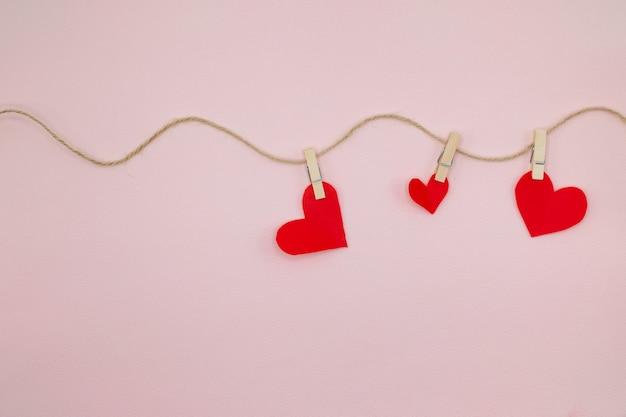 Priorità bassa di giorno di san valentino con cuori rossi che appendono sul clothesline.