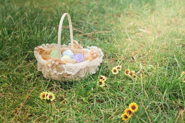 Priorità bassa di pasqua dell'annata con le uova decorate in un cestino sull'erba e sui fiori