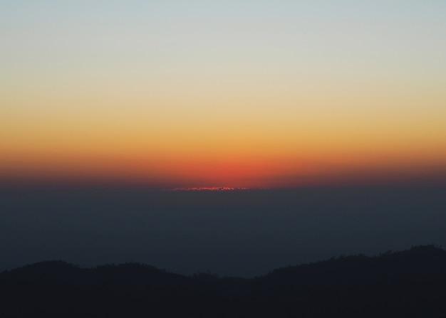 Priorità bassa drammatica della montagna e del cielo prima dell'alba di mattina