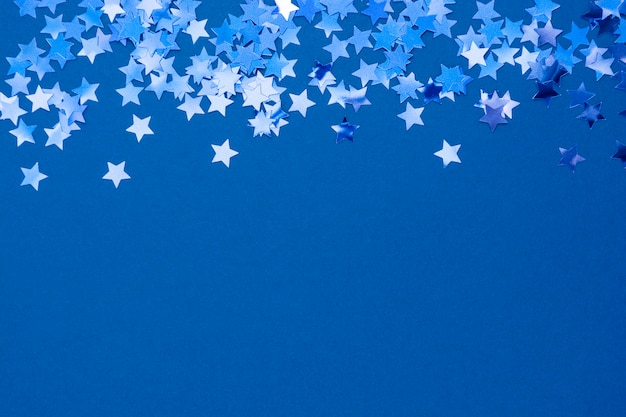 Priorità bassa o struttura astratta blu di natale con i coriandoli delle stelle su priorità bassa blu. spazio per il testo.