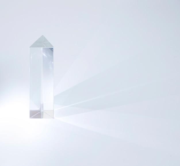 Prisma di cristallo lucido che emette luce su sfondo bianco
