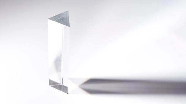 Prisma di cristallo trasparente con ombra scura su sfondo bianco