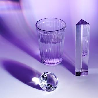 Prisma; diamante scintillante e bicchiere d'acqua su fondo lucido viola