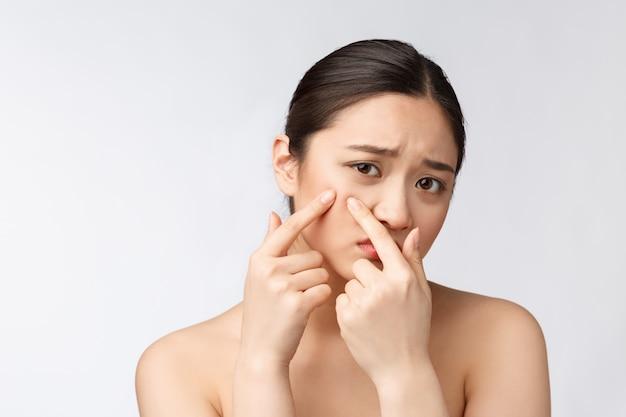Problema di pelle del fronte - la giovane donna infelice tocca la sua pelle isolata, concetto per cura di pelle, asiatica