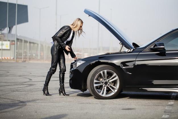 Problemi sulla strada. donna con l'automobile rotta che rivolge allo smartphone