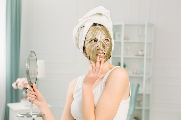 Procedura cosmetica maschera d'oro nel salone di bellezza. attraente ragazza sexy con asciugamano bianco toccando il viso e maschera d'oro sul viso, con in mano uno specchio.