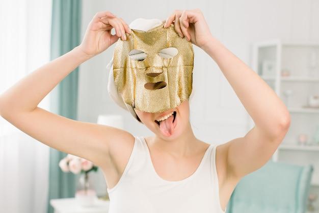 Procedura cosmetica, ragazza abbastanza divertente in asciugamano bianco con maschera di lamina d'oro su spazio leggero. bellezza, spa, cura della pelle e del corpo.