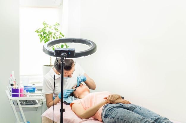 Procedura di laminazione delle ciglia. colorazione, arricciatura, laminazione, lifting delle ciglia. extension ciglia. allungamento delle ciglia per la ragazza nel salone di bellezza