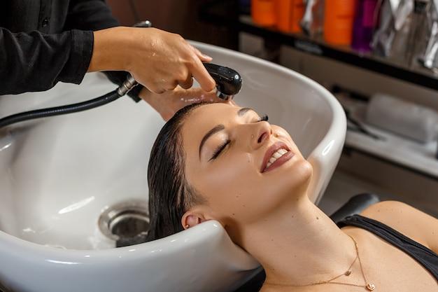 Procedura di lavaggio bella giovane donna con la testa di lavaggio parrucchiere al parrucchiere.