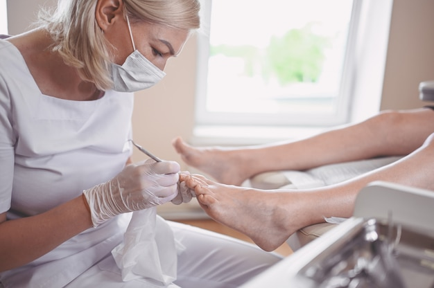 Procedura di pedicure medica professionale da vicino con doppio strumento per unghie