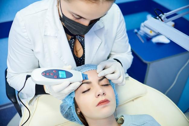Procedura di pulizia del viso. scrubber ad ultrasuoni. il concetto di trattamento e cura della pelle.