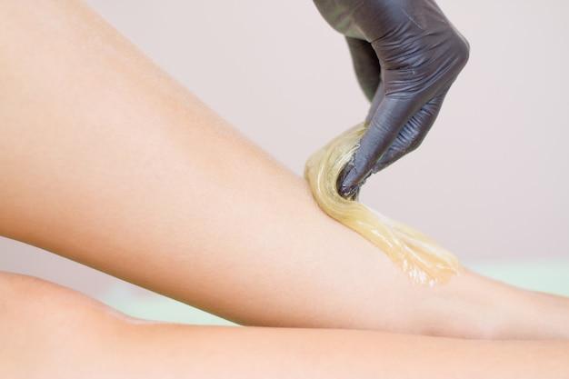 Procedura di rimozione dei capelli sulla gamba bella donna con pasta di zucchero o miele di cera e guanti neri a mano