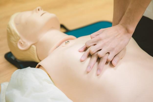 Procedura medica di addestramento alla rcp - dimostrazione delle compressioni toraciche sulla bambola cpr nella classe
