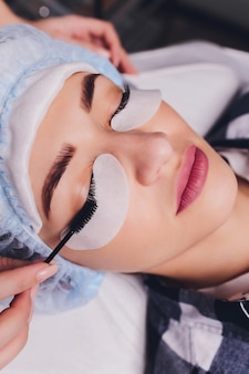 Procedura per l'estensione delle ciglia. primo piano vista dell'occhio femminile con lunghe ciglia. stilista con pinzette rosa, pinze e ciglia allungate. messa a fuoco selettiva, macro. concetto di bellezza. trattamento.
