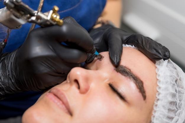Procedure cosmetiche per il trattamento delle sopracciglia. microblading nel salone di bellezza. cosmetologia professionale il processo di applicazione del pigmento, modellatura delle sopracciglia, sopracciglia permanenti di trucco, tatuaggio