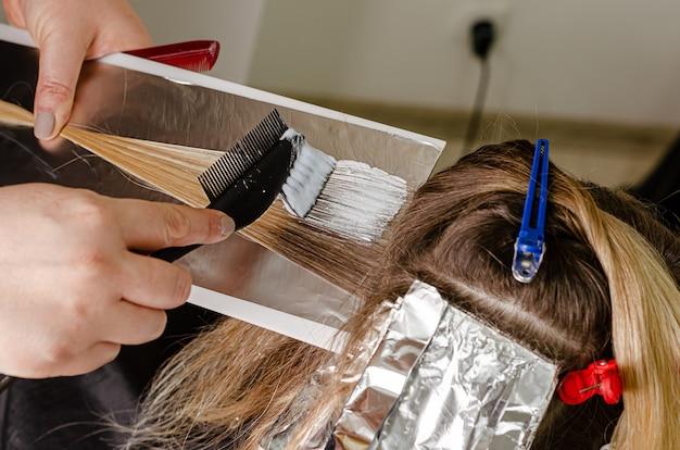 Processo di applicazione di candeggina in polvere sui capelli dei clienti e avvolgimento nella lamina. tecnica airtouch