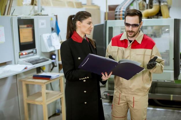 Processo di controllo della giovane donna nella fabbrica con il lavoratore maschio
