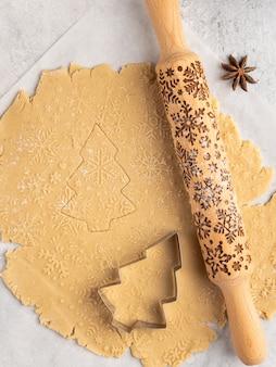 Processo di cottura di dolci tradizionali di natale e capodanno, biscotti di panpepato, mattarello con motivo a fiocchi di neve su di esso, stelle di anice e cannella, natale e inverno, disposizione della cornice