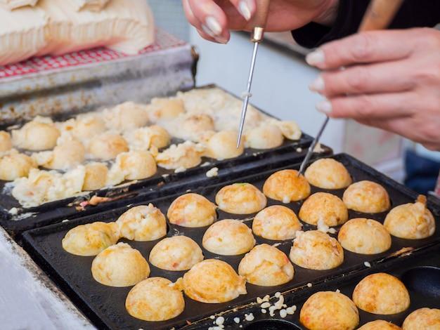 Processo di cottura di gnocchi di palla takoyaki su una padella calda. takoyaki è uno snack giapponese molto famoso in giappone.