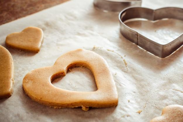 Processo di creazione di biscotti allo zenzero sotto forma di cuori su un tavolo di legno