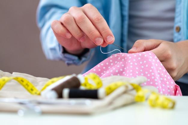 Processo di cucito. la casalinga cuce a casa usando l'ago e vari accessori per cucire