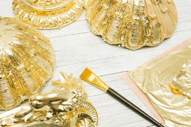 Processo di doratura. foglia d'oro, pennello e modanature sul tavolo luminoso