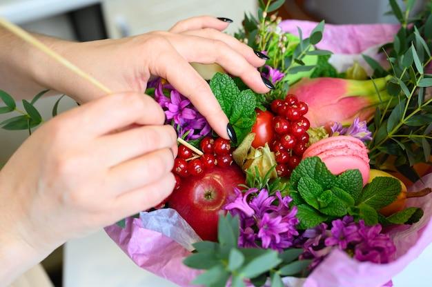 Processo di formazione di un bouquet di frutta e fiori.