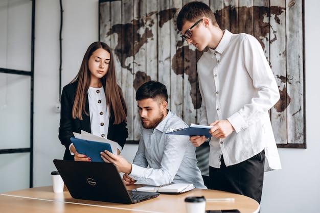 Processo di lavoro di squadra. giovane imprenditore lavora con un nuovo progetto di avvio in ufficio. donna che tiene la carta in mano, l'uomo con la barba lo vede.