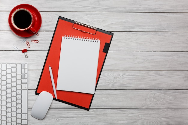 Processo di lavoro rosso del mouse della tastiera dell'orologio della tazza di caffè del taccuino della cartella dello scrittorio del bordo bianco