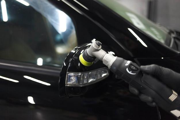 Processo di lucidatura di specchietti per auto con lucidatrice e cera. rimozione dei graffi dalla carrozzeria