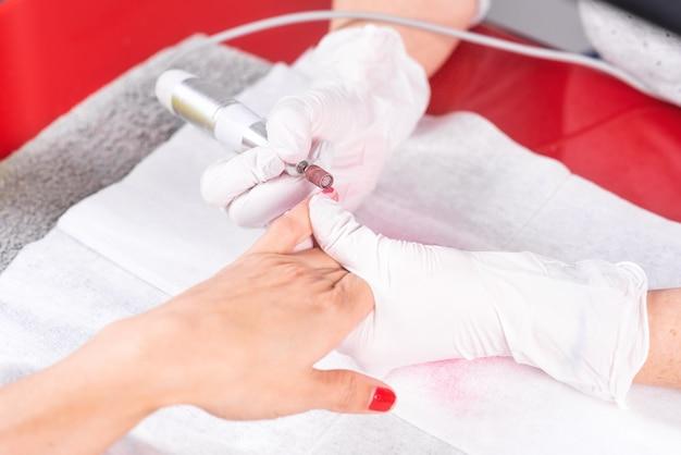 Processo di manicure professionale, pulizia delle unghie con una fresa per manicure