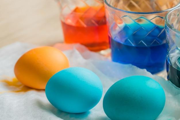 Processo di morte dell'uovo di pasqua. tazze di vetro trasparente con acqua colorata
