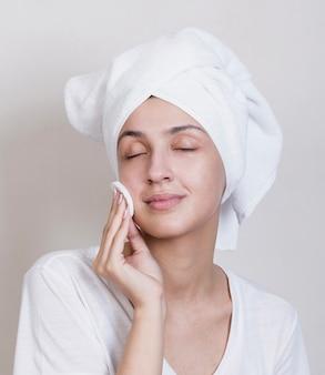 Processo di pulizia viso giovane donna