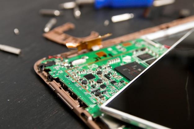 Processo di riparazione del dispositivo tablet pc vicino a cacciavite e punta. smontato.