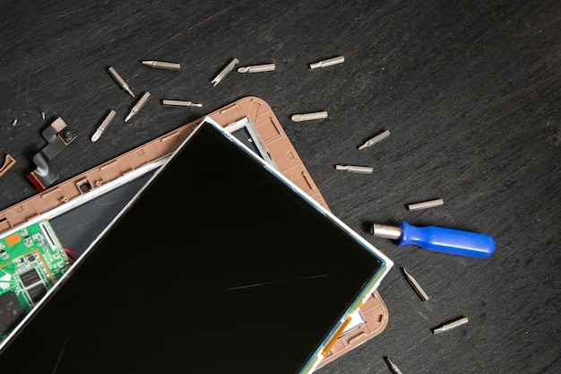 Processo di riparazione del dispositivo tablet pc vicino a cacciavite e punta su superficie di legno nera smontata