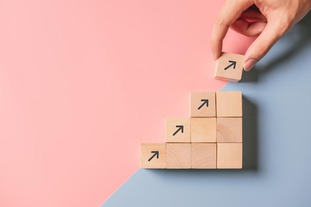 Processo di successo di crescita del concetto aziendale. chiuda sulla mano dell'uomo che sistema l'impilamento del blocco di legno come scala di punto sull'azzurro e sul rosa di carta