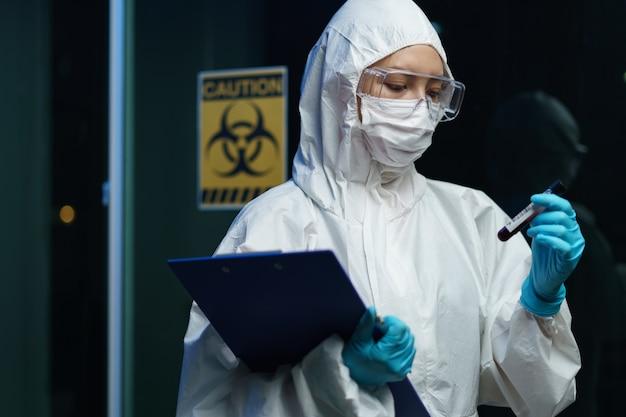 Processo di test del coronavirus: scienziata che indossa una maschera medica con occhiali di sicurezza in tuta ignifuga, con in mano una provetta per campioni di analisi del sangue con informazioni sull'analisi del sangue.