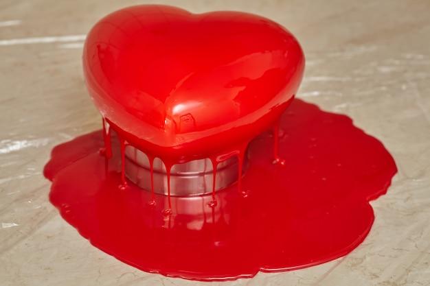 Processo di versamento della glassa rossa sul dolce a forma di cuore