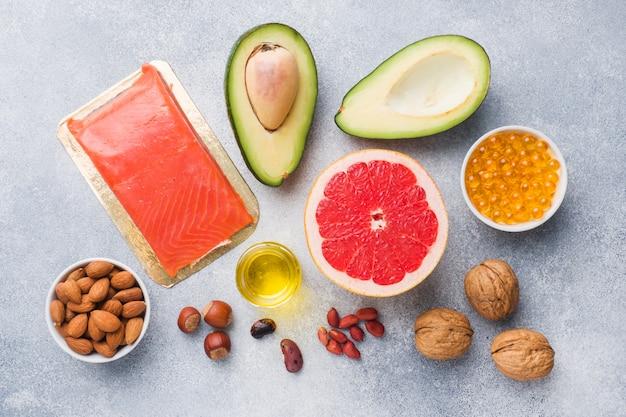 Prodotti antiossidanti alimentari sani: pesce e avocado, noci e olio di pesce, pompelmo su sfondo grigio cemento.