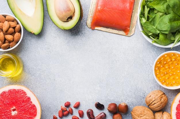 Prodotti antiossidanti alimentari sani: pesce e avocado, noci e olio di pesce, spinaci e olio di pompelmo su uno sfondo di cemento grigio. copia spazio