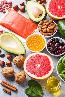 Prodotti antiossidanti alimentari sani: pesce e avocado, noci e olio di pesce, spinaci e olio di pompelmo su uno sfondo di cemento grigio.