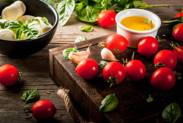 Prodotti biologici crudi dell'azienda agricola. preparazione della cena in stile italiano. ingredienti per insalata caprese, pasta, pizza. basilico, pomodori, mozzarella, olio d'oliva su un vecchio tavolo di legno.