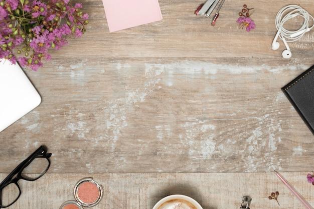 Prodotti cosmetici; accessori personali con pianta disposti su scrivania in legno