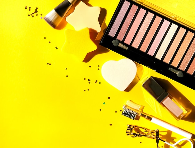 Prodotti cosmetici assortiti, palette di ombretti, lucidalabbra, pettine per soffio, arricciacapelli, pennello e spugne su sfondo giallo. concetto di bellezza. design piatto.