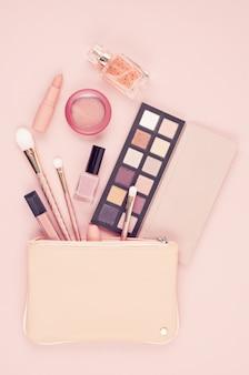 Prodotti cosmetici di trucco su sfondo rosa pastello, piatto laico, vista dall'alto