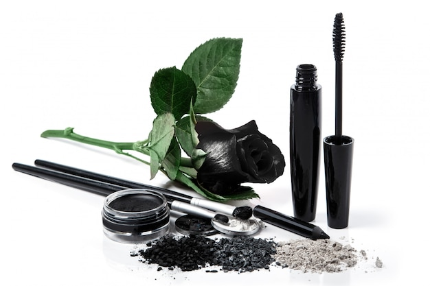 Prodotti cosmetici e rosa nera su sfondo bianco