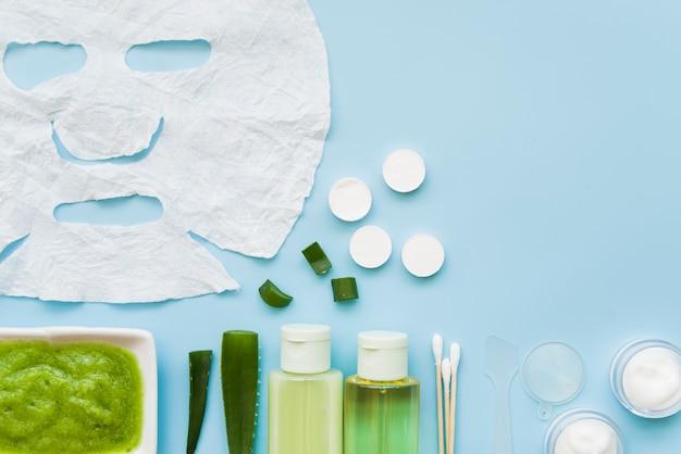 Prodotti cosmetici naturali con foglio di carta bianca viso su sfondo blu