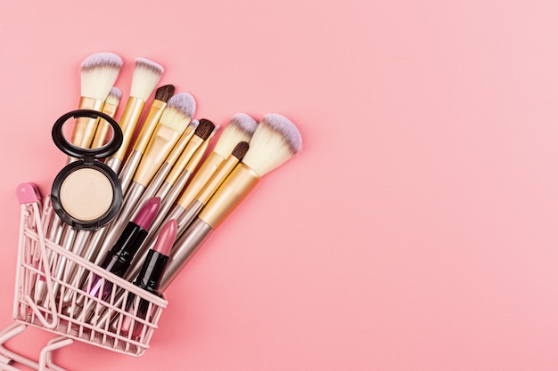 Prodotti cosmetici nel carrello della spesa sulla parete rosa